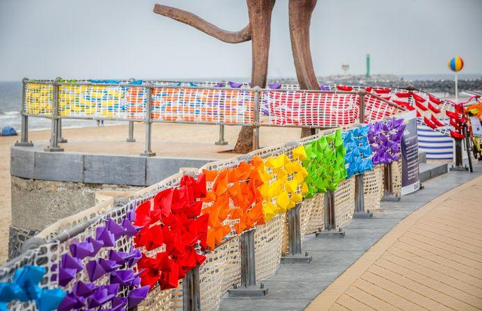 Op de zeedijk van Oostende vormen 3.000 papieren bootjes de regenboogvlag.