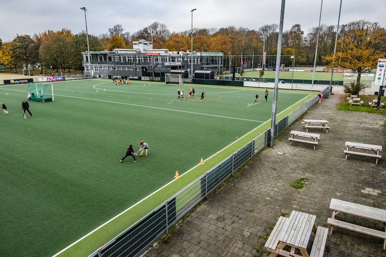 De velden van hockeyclub Amsterdam. In hoek van het clubhuis hangt een plaquette met de namen van elf leden van de club die in de Tweede Wereldoorlog zijn gesneuveld. Beeld Joris Van Gennip