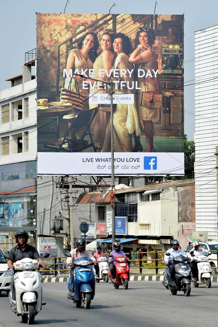 Een poster met een van Facebooks credo's: Live What You Love hangt in de straten van Bangalore. Beeld AFP