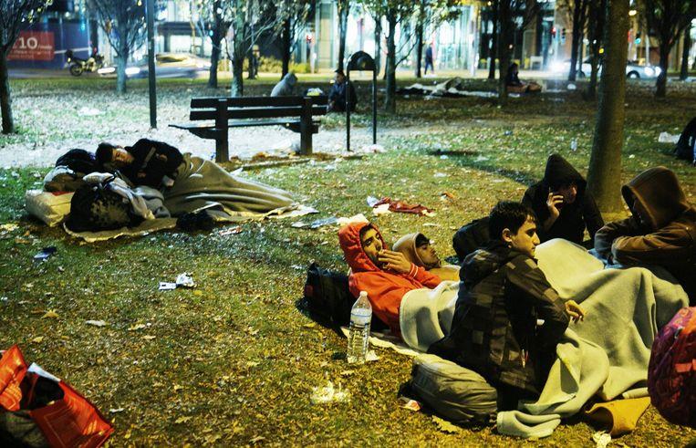 Vluchtelingen slapen in het parkje tegenover het WTC III-gebouw. Beeld Tim Dirven