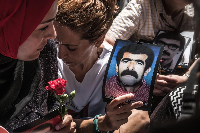 Met foto's van verdwenen familieleden en rode anjers vragen de Zaterdagmoeders elke zaterdag aandacht voor hun zaak. Beeld Joris Van Gennip