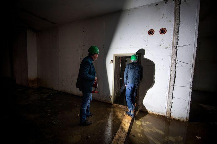 Projectontwikkelaar Gerard Assen (links) en bunker-enthousiasteling Bert Nijkamp nemen een kijkje in de donkere ruimte onder het oude stadhuis.