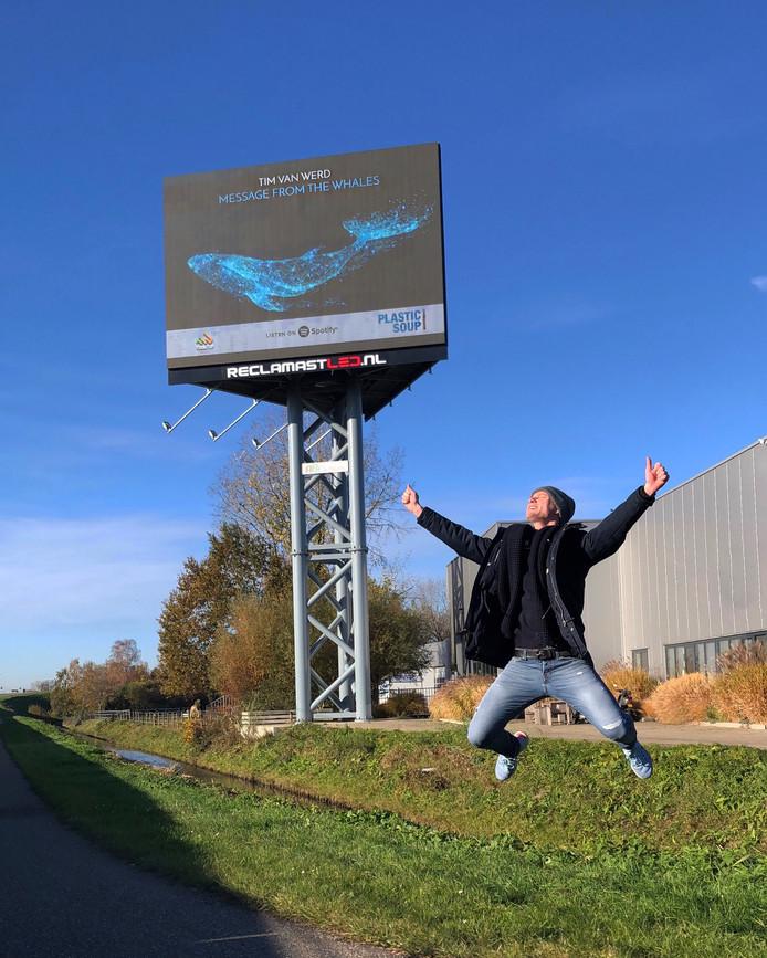 Dj en producer Tim van Werd bij een reclamezuil langs de A15 waar reclame wordt gemaakt voor zijn nummer.