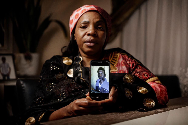 De moeder van Lamine Bangoura, Marthe Millimono met een foto van haar zoon.  Beeld Eric de Mildt