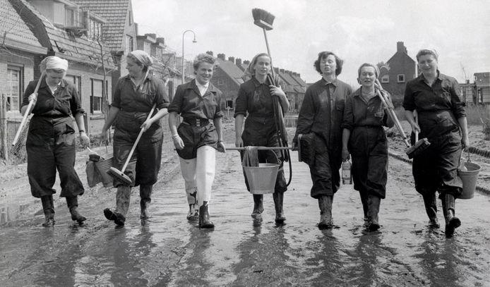 Zeven vrouwen in overall en op rubberlaarzen, gewapend met bezems en emmers zijn onderweg om huizen en andere gebouwen in Kruiningen schoon te maken na de Watersnoodramp.