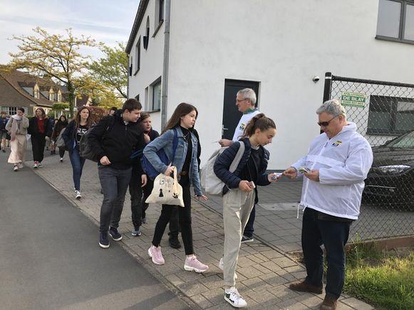 De leden van Vlaams Belang delen flyers uit.