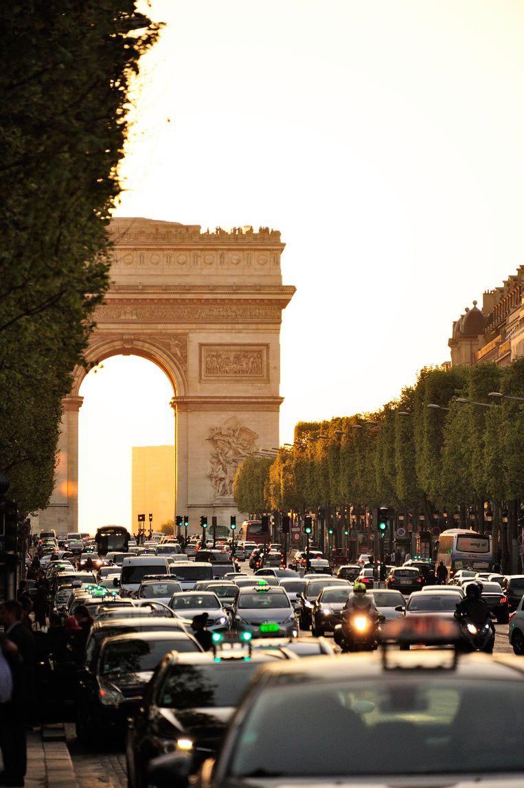 Files op de Champs-Elysées. In 2030 mogen er enkel nog schone en stille wagens rond de Arc de Triomphe rijden. Beeld ONLY FRANCE
