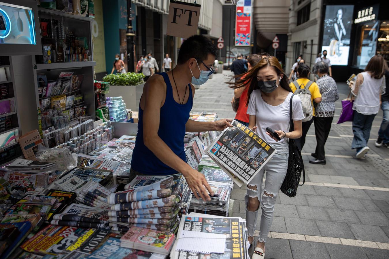 Een vrouw koopt vrijdagochtend een exemplaar van de prodemocratische krant Apple Daily bij een kiosk in Hongkong, een dag nadat de politie een inval deed op de redactie en vijf leidinggevenden arresteerde.