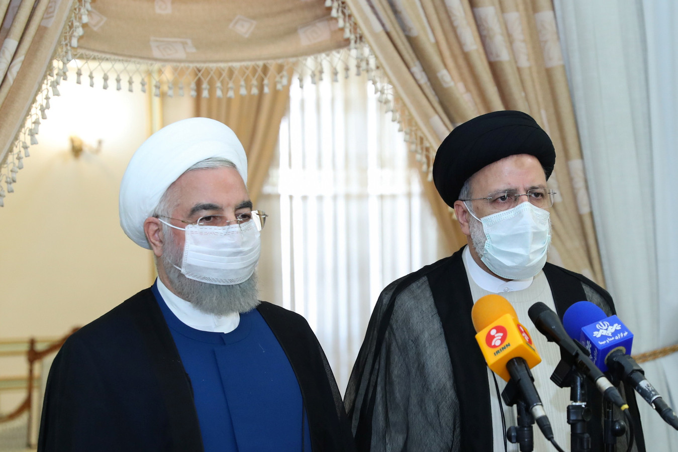 Vertrekkend president Hassan Rouhani (links) en de nieuwe president Ebrahim Raisi op een persconferentie zaterdag.