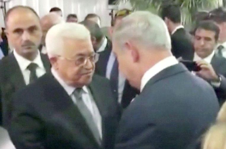 Een beeld uit een video waarop de Palestijnse president Mahmoud Abbas de hand schudt van de Israëlische premier Benjamin Natanyahu, vanochtend in Jeruzalem. Beeld REUTERS