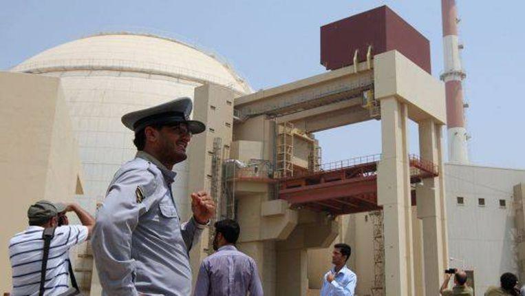 Een Iraanse beveiliger en een stel journalisten bij een kernreactor in Zuid-Iran. Die werd vorige week aangevallen door de worm Stuxnet. (AFP) Beeld