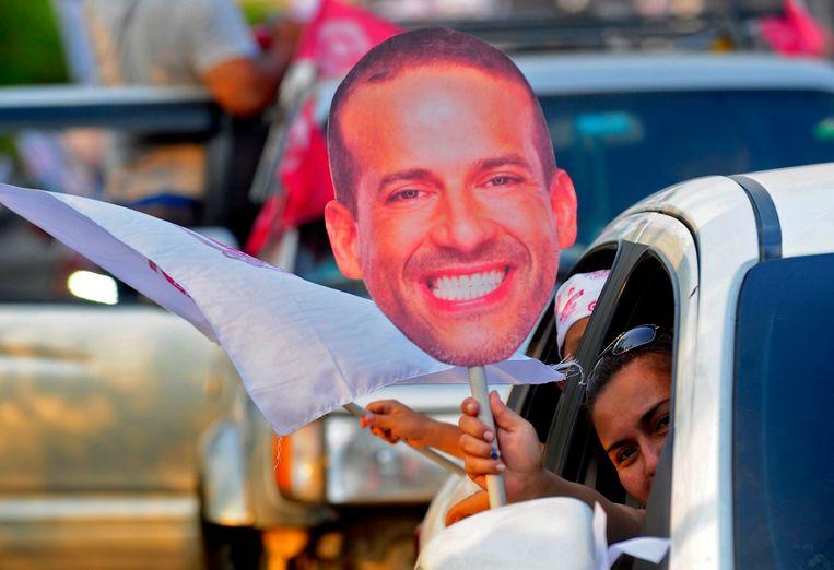 Een supporter van Luis Fernando Camacho toont een plakaat van zijn hoofd vanuit de auto in een rally voor de rechtse presidentskandidaat. Beeld AFP
