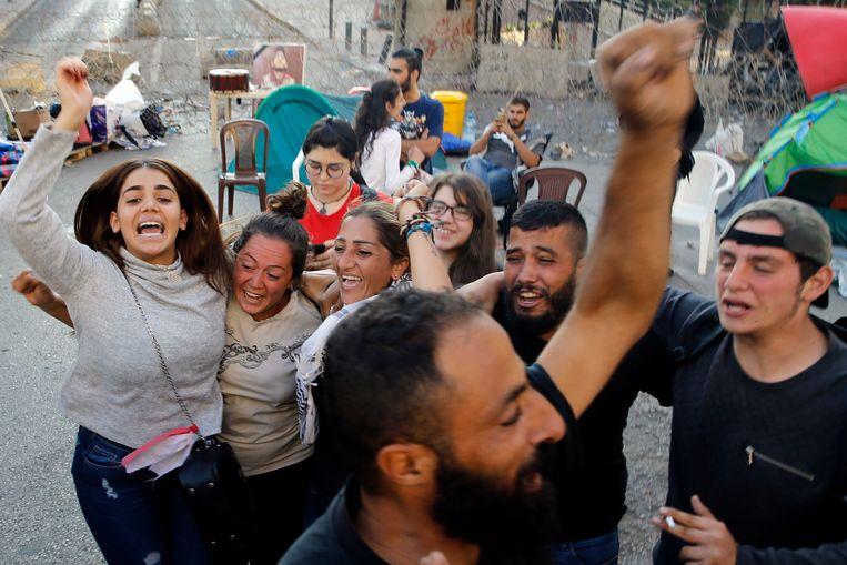 Demonstranten vieren feest nadat Hariri zijn aftreden heeft bekendgemaakt. Beeld AP