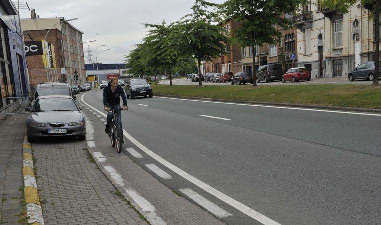 Een fietser maakt gebruik van het pad(je) langs de Schaarbeeklei, net naast de drukke baan zelf.
