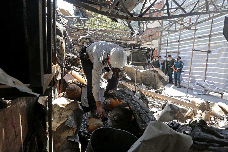 Een brandweerman onderzoekt de ruïne van een ziekenhuis in Teheran. Bij een ontploffing vielen daar negentien doden. Beeld AFP
