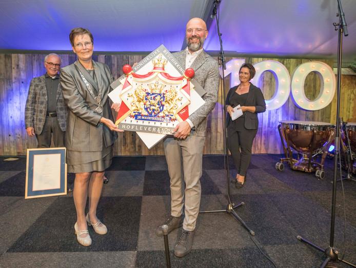 Een trotse directeur Hermen Bouman (rechts) toont samen met burgemeester Ger van de Velde (links) het schild dat hoort bij het predikaat Hofleverancier. Op de achtergrond Boumans echtgenote Jessica (rechts) en zijn vader Arie (links).