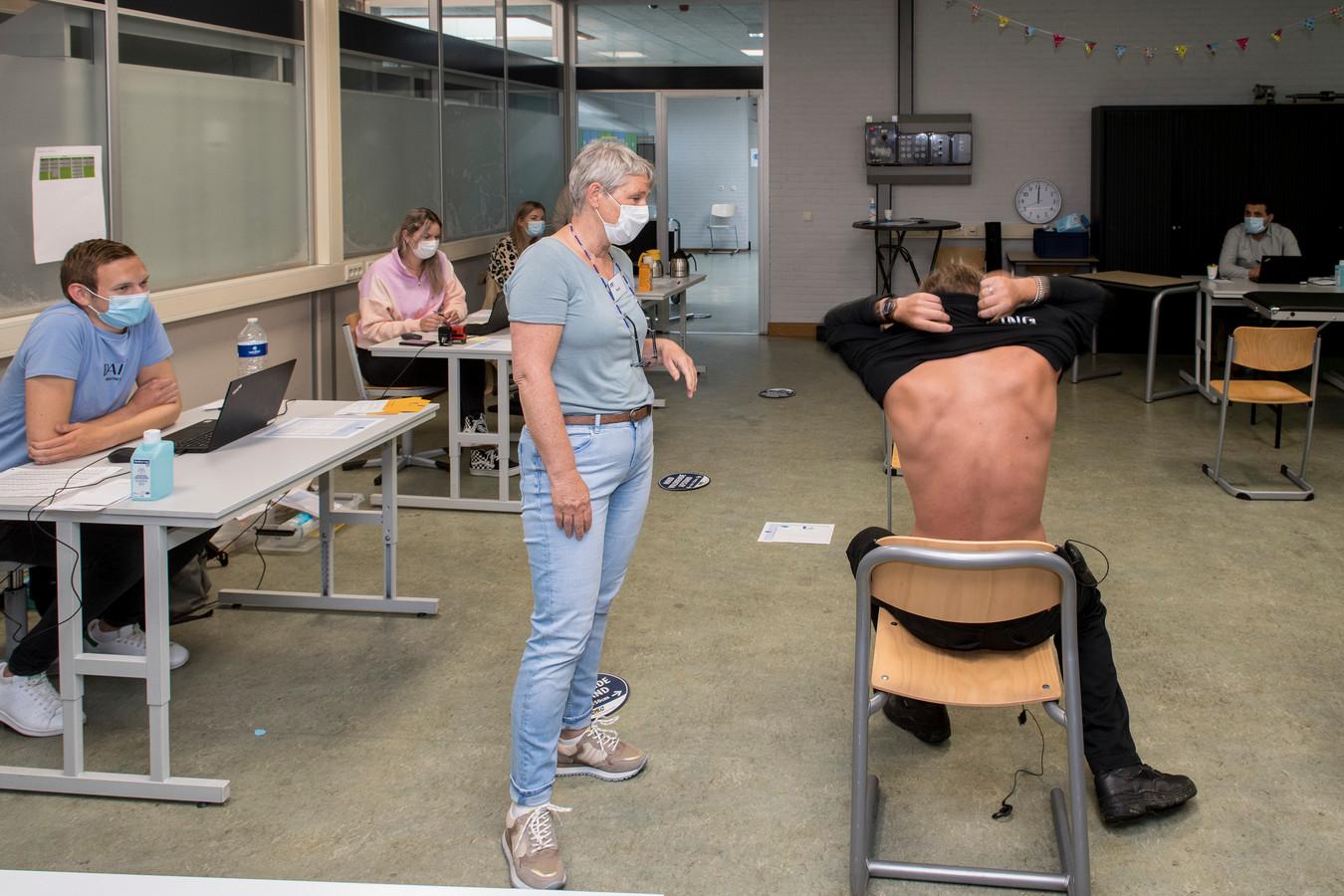 Marchano van Dee (18) trekt zijn trui uit om zich te laten vaccineren.
