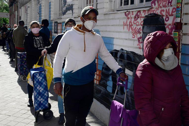 Door de lockdown werd de precaire situatie waarin veel Spanjaarden (en immigranten) leven pijnlijk zichtbaar: overal in het land ontstonden 'colas de hambre', hongerrijen, van mensen die de dagelijkse boodschappen niet meer konden betalen.  Beeld AFP