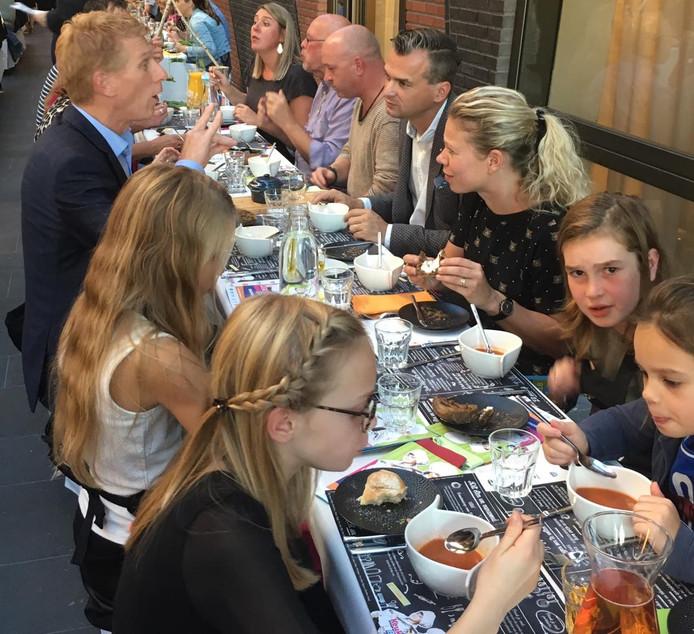 Kinderen smullen van gerechten op basis van hun eigen Keukenbazen-recepten. Ook burgemeesters eten mee, onder wie Marnix Bakermans van Landerd (linksboven).