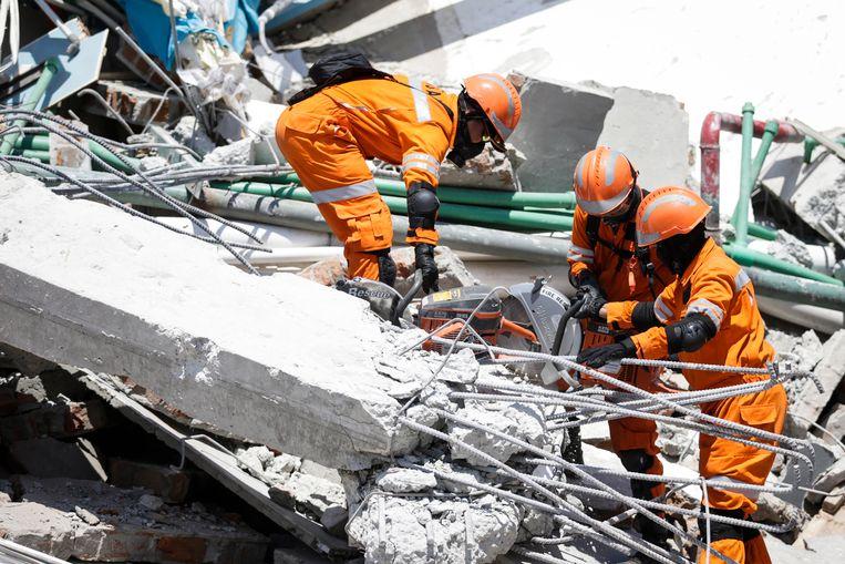 Indonesische reddingswerkers aan het werk op de resten van het Roa Roa-hotel.