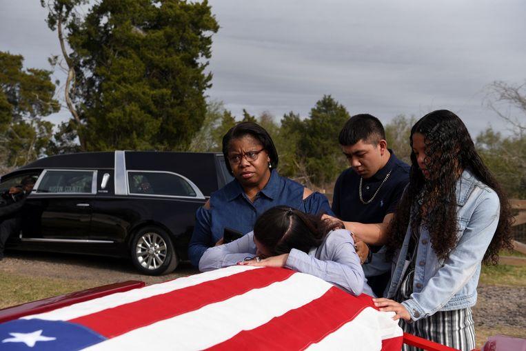 Een Amerikaanse familie neemt afscheid van hun aan Covid-19 overleden vader en echtgenoot. Foto van begin dit jaar. Beeld REUTERS