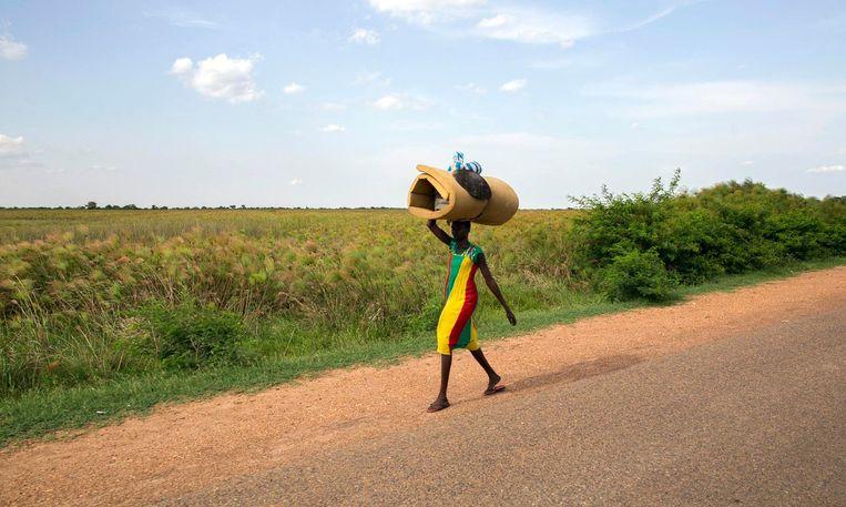 Een vrouw draagt haar bezittingen op haar hoofd terwijl ze vlucht voor aanvallen in Bentiu. Beeld null