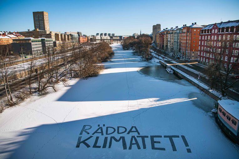 'Red het klimaat!' staat in de sneeuw geschreven op een kanaal in Stockholm.  Beeld AFP