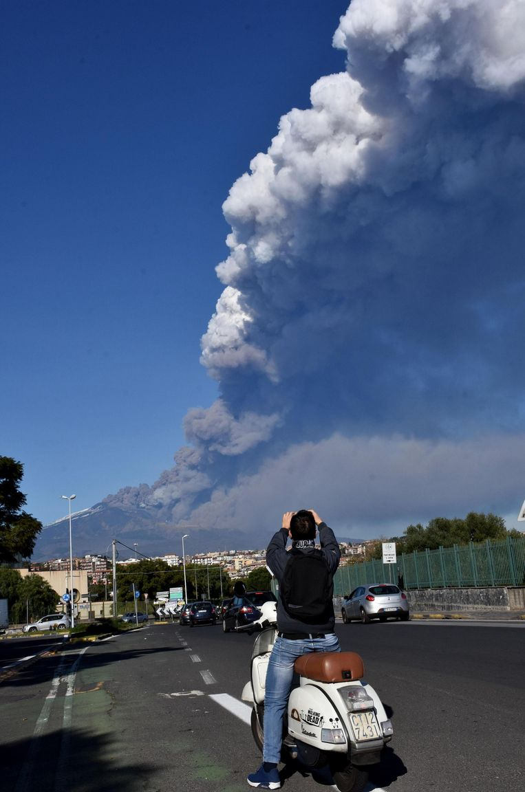 epaselect epa07247469 A man takes a photo of a rising plume of smoke coming from Etna volcano in Catania, December 24th 2018. An eruptive fracture opened this morning on Mount Etna at the base of the southeast crater, where explosive activity continues.  EPA/ORIETTA SCARDINO Beeld EPA