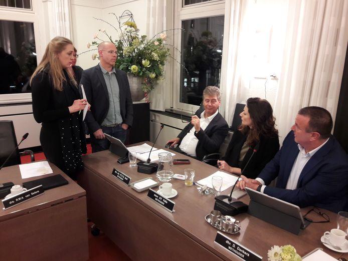 Anne-Cristien Spekle (VVD) en Carlo van Esch (PGB) voeren in 2019 tijdens een schorsing overleg met de wethouders Peter Smit, Stefanie Vatta en Dion Dankers (vlnr).