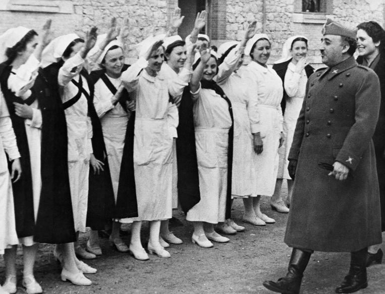 Verpleegsters brengen de nationalistische groet aan generaal Francisco Franco (1892-1975), de leider van de nationalistische strijdkrachten van Spanje die de Republikeinse regering versloeg na drie jaar burgeroorlog (1936-1939). Spanje, 1938.  Beeld Corbis via Getty Images