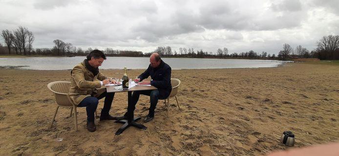 Hendrik Jan Mensink (links) en wethouder Ted Kok ondertekenen de papieren op het strand van de Slingeplas.