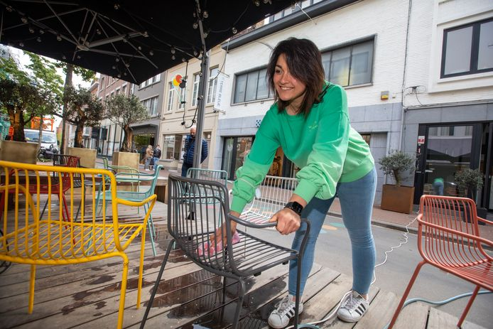 Uitbater Tiana van 'Osteria Moretti' geeft haar kleurrijke terrasstoelen een stevige schoonmaakbeurt.
