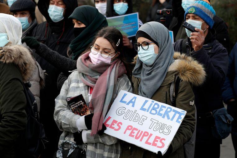 Twee vrouwen demonstreren in Parijs tegen de strenge anti-islamwet, die niettemin door het Franse parlement werd aangenomen.  Beeld AFP