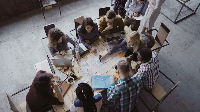 Top view of creative business team sitting at the table at loft office and working. Woman manager brings the document to mixed race group of people. Colleagues discussing the project. Beeld Thinkstock