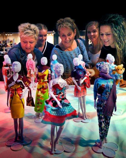 Zussen Ellen (links) en Evenlien (midden) bekijken met anderen de poppenkleertjes van Dress your Doll.