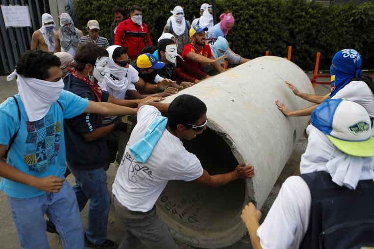 Demonstranten verplaatsen een betonnen pijp om een barricade te bouwen. Beeld reuters