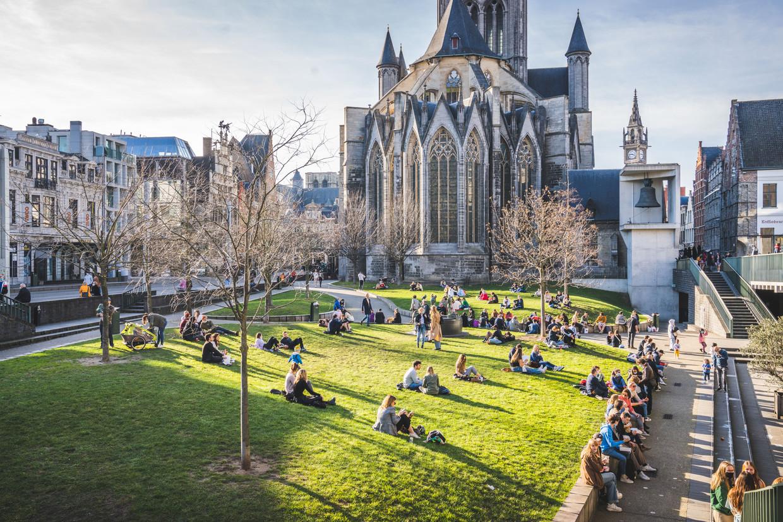 Mensen genieten in kleine groepjes van de lentezon in Gent. Beeld Wannes Nimmegeers