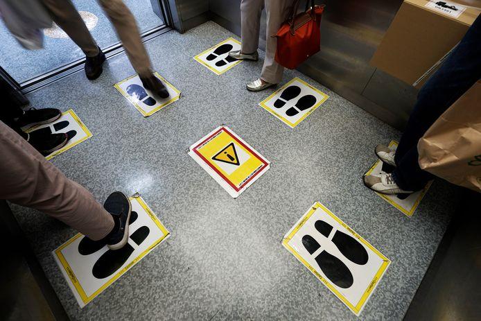 Stickers op een liftvloer moeten zorgen dat iedereen zich aan de afstandsregels houdt.