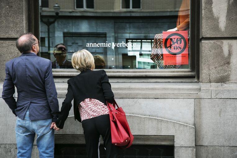 Uit onvrede met de komst van COS prijken op veel etalages in de Dansaertstraat affiches met de slogan 'No COS'. Beeld Tim Dirven