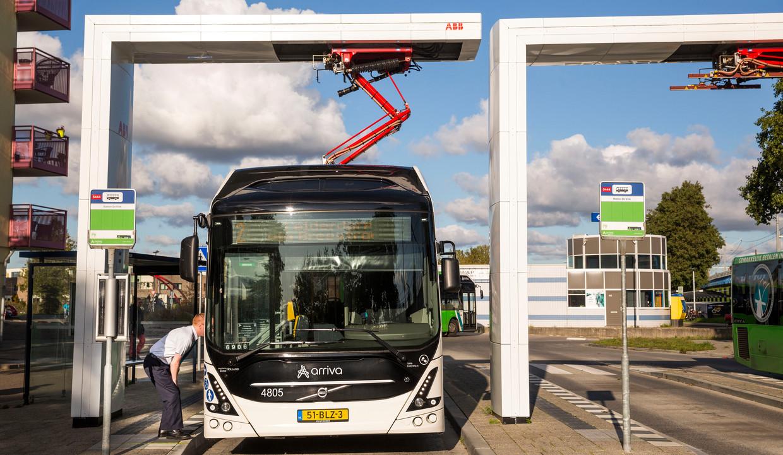 Bussen van Arriva laden op bij station Leiden De Vink via een zogenaamde pantograaf. In andere gemeenten steken chauffeurs een stekker in hun bus bij een laadpaal, zoals bij elektrische auto's. Beeld Arie Kievit