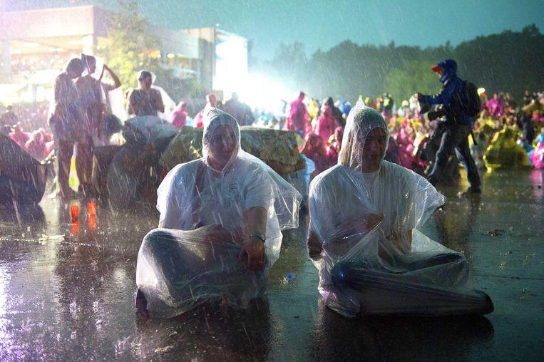 epa04247077 Visitors wear rain ponchos during heavy rain and thunder at the 45th annual Pinkpop music festival in Landgraaf, The Netherlands, 09 June 2014. The event ends on 09 June.  EPA/MARCEL VAN HOORN Beeld EPA