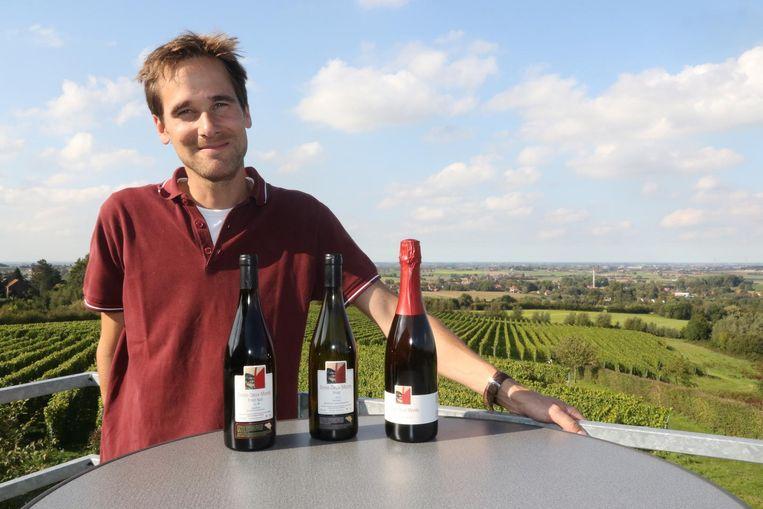 Martin Bacquaert toont de winnende wijnen op zijn domein. Met de linkse houtgelagerde Pinot Noir 2016 won hij zilver. Met de twee rechtse wijnen, de witte Pinot 2016 en de mousserende Wiscoutre, behaalde hij een gouden medaille.
