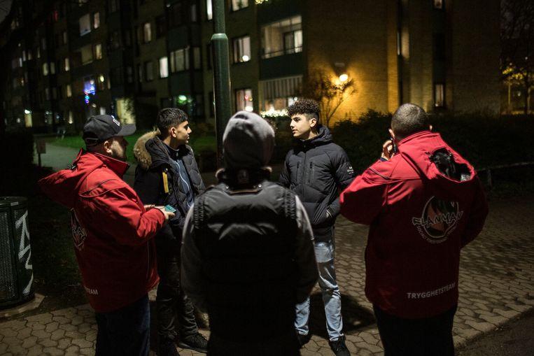 Jeugdwerkers zijn in gesprek met jongens die op straat rondhangen in de wijk Bellevuegård. De jeugdwerkers zijn in dienst bij stichting Flamman die verschillende projecten en inrichtingen in de buitenwijken van Malmö heeft.  Beeld Julius Schrank / De Volkskrant