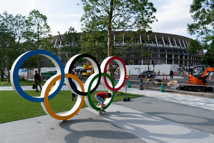 Het stadion waar de openingsceremonie van de Olympische Spelen van 2020 in Tokio wordt gehouden met op de voorgrond de olympische ringen.