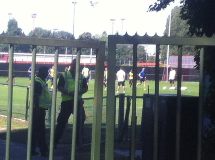 Op de voorgrond traint een groepje spelers van RKC Waalwijk. Achter het doek speelt zich de wedstrijd tussen Feyenoord en de Waalwijkse club af.