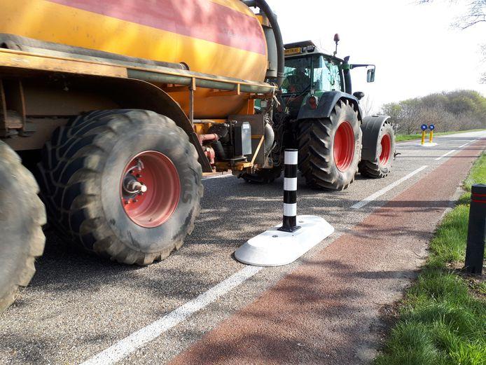 Een trekker met gierton slingert door de dubbele wegversmalling op de Bosschebaan in Heesch.