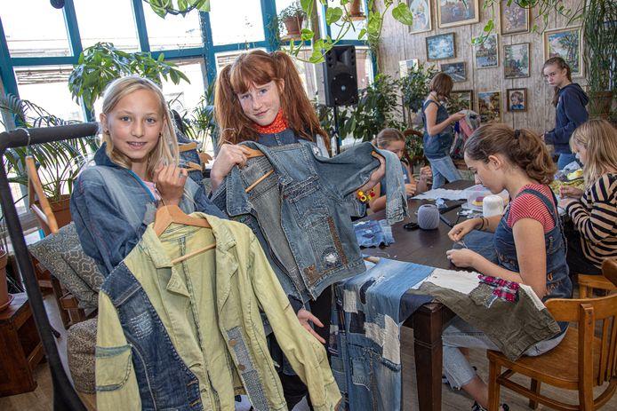Meike de Vries (13) en Serafina van Damme (11) tonen hun creaties. Achter hen de overige tieners van Fashion Rebels.