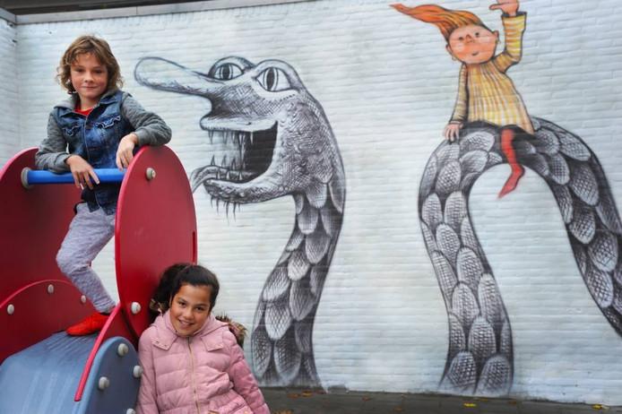Sam (links òp de glijbaan) en Celeste zijn niet bang voor de stoorworm. Ze vinden het wel cool dat er vrolijke muurschilderingen vlakbij hun scholen én nog dichter bij de nieuwe opvang, het Koraal, zijn te bewonderen.