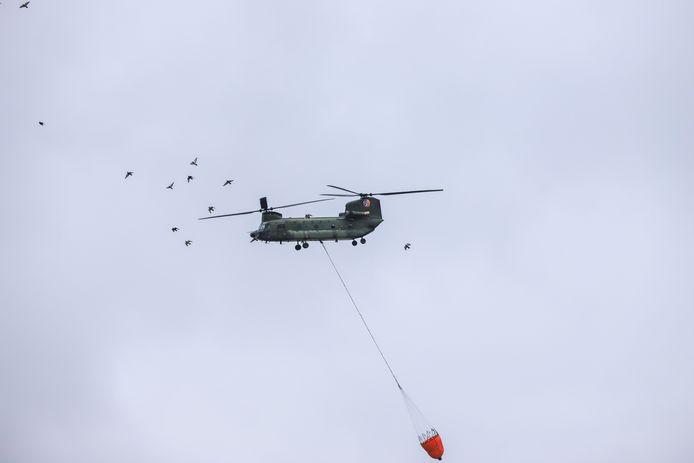 Defensie helikopter vliegt af en aan met water naar brand in Den Bosch