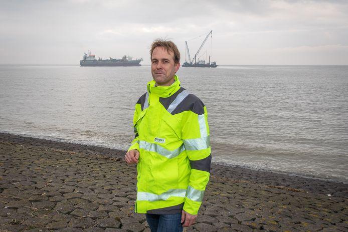Maarten Bruggeman van TenneT geeft op de zeedijk bij Borssele uitleg over wat baggerschip Prins der Nederlanden en kraanponton DIna M precies aan het doen zijn.